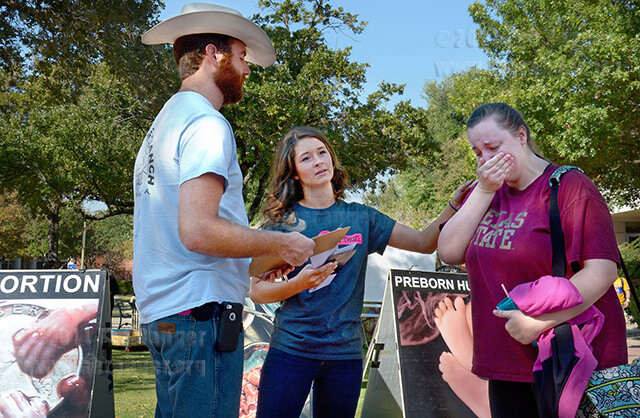 Lindsey Bell comforts mass communications sophomore Kelley Jaskinia, who began to cry as she talked about her stance against abortion today in the mall. Nate Hubert and Bell, volunteers for Love of Truth Ministries, will be in the mall today until 2:30 p.m. Their goal is to bring awareness and have an open dialogue with students about abortion. Photo by Neven Jones
