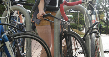 """Biology freshman Karina DeLeon locks her bike using a U-lock Wednesday before class in the mall east of the chemistry and geology building. DeLeon said she recommends students """"buy an expensive lock"""" to guard against theft.  Photo by David Guel"""