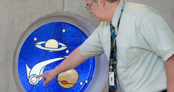"Bob Kelley points to a comet flying through the sky today in a mosaic window he designed and created for the Scobee Education Center. The ""children's window"" also shows Saturn and Venus. Kelley is creating a total of four windows.  Photo by Neven Jones"