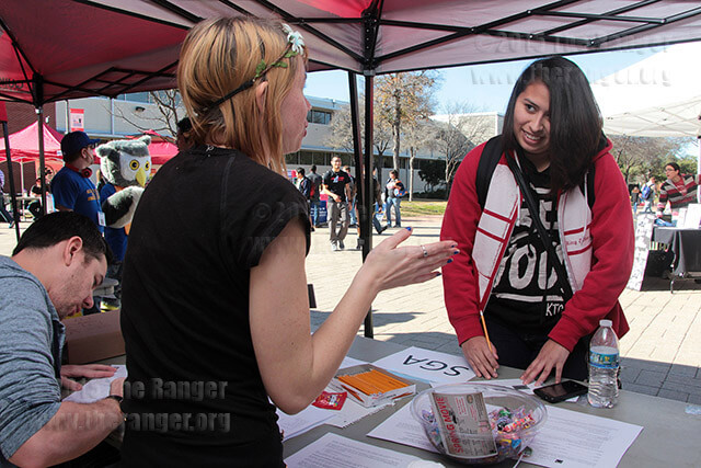 Harley Williams, psychology sophomore and Student Government Association vice president, tells biology freshman Isabel Rodriguez about SGA while Rodriguez completes a survey during the Student Organization Showcase Wednesday in the mall.  Photo by E. David Guel