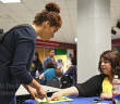 Gloria Hymer, Parker School Uniforms store manager, points at the location where civil engineering freshman Crista Cerda can pickup a job application April 14 at the Career Fair in the Fiesta Room of Loftin. Parker was one of 34 employers represented at the fair. Cerda said the fair was helpful in her search for a summer job.  Photo by Daniel Carde